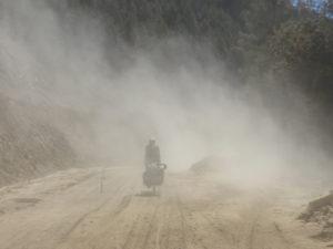 China, Ost Tibet, Bettina wird von der Staubwolke eines LKWs verschluckt